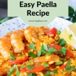 Side view of an easy shrimp paella with lemon and parsley to garnish.