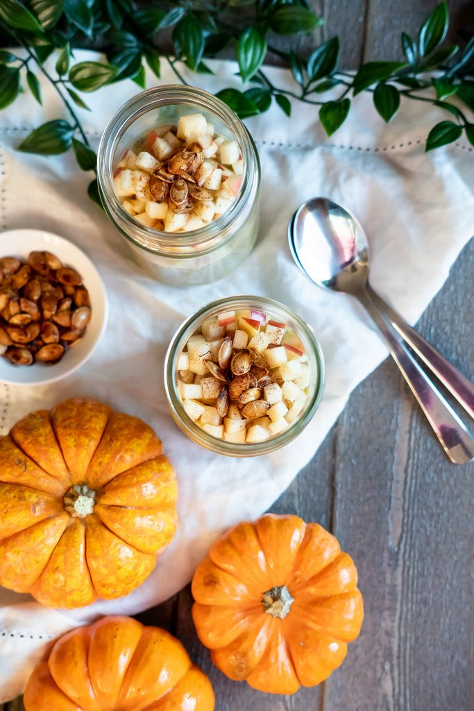 Overhead view of two tasty Pumpkin Chia Puddings topped with apples and pumpkin seeds with Fall decorations.