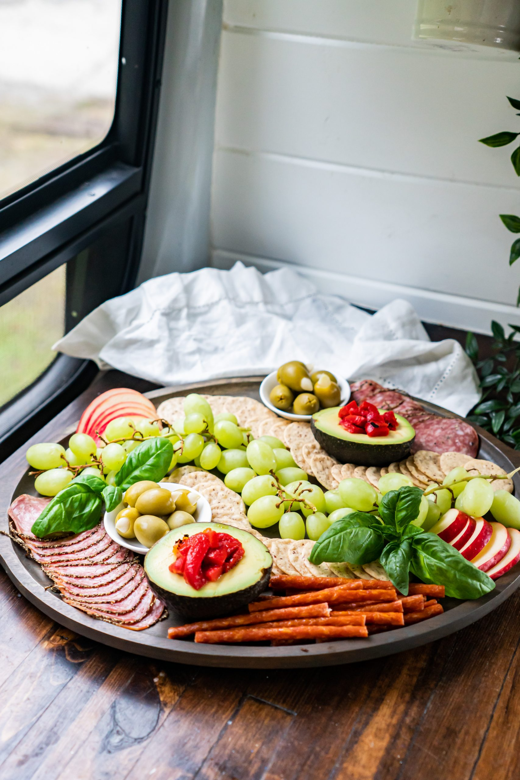A gluten and dairy free charcuterie board resting on a counter in my camper van kitchen.