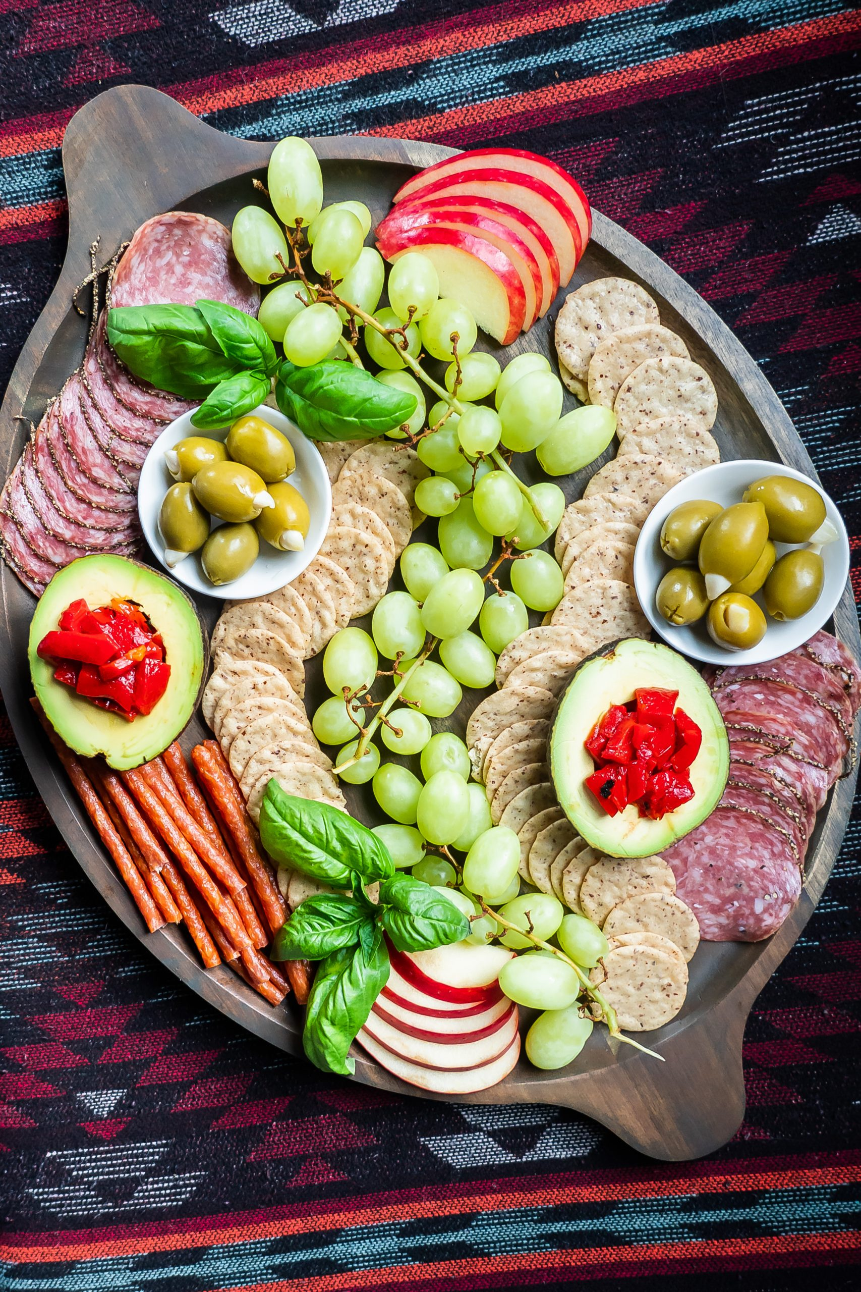 A gluten and dairy free charcuterie board with grapes, crackers, meats, and other nibbles.