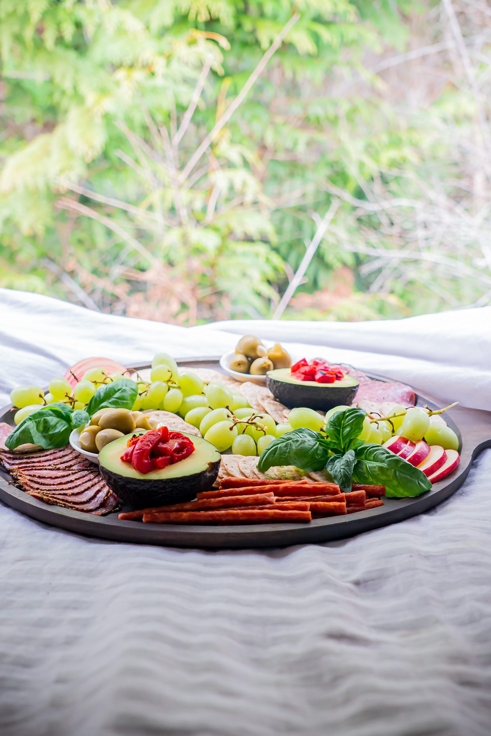 A gluten and dairy free charcuterie board set on a bed with a view of foliage outside.