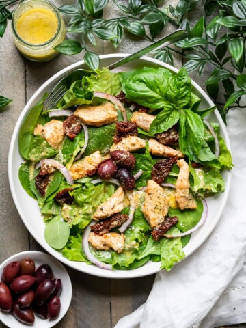 Tuscan Chicken Salad on a plate with fresh basil leaves, dressing in a jar, and kalamata olives.