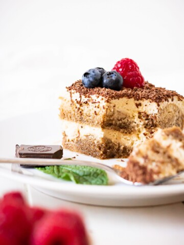 Hero image of a slice of dairy free tiramisu with fresh berries on top and a piece of chocolate with a mint leaf on the side of the plate.