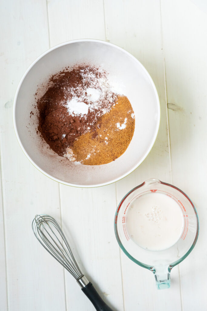 Vegan buttermilk in a liquid measuring cup and a large mixing bowl with dry ingredients.