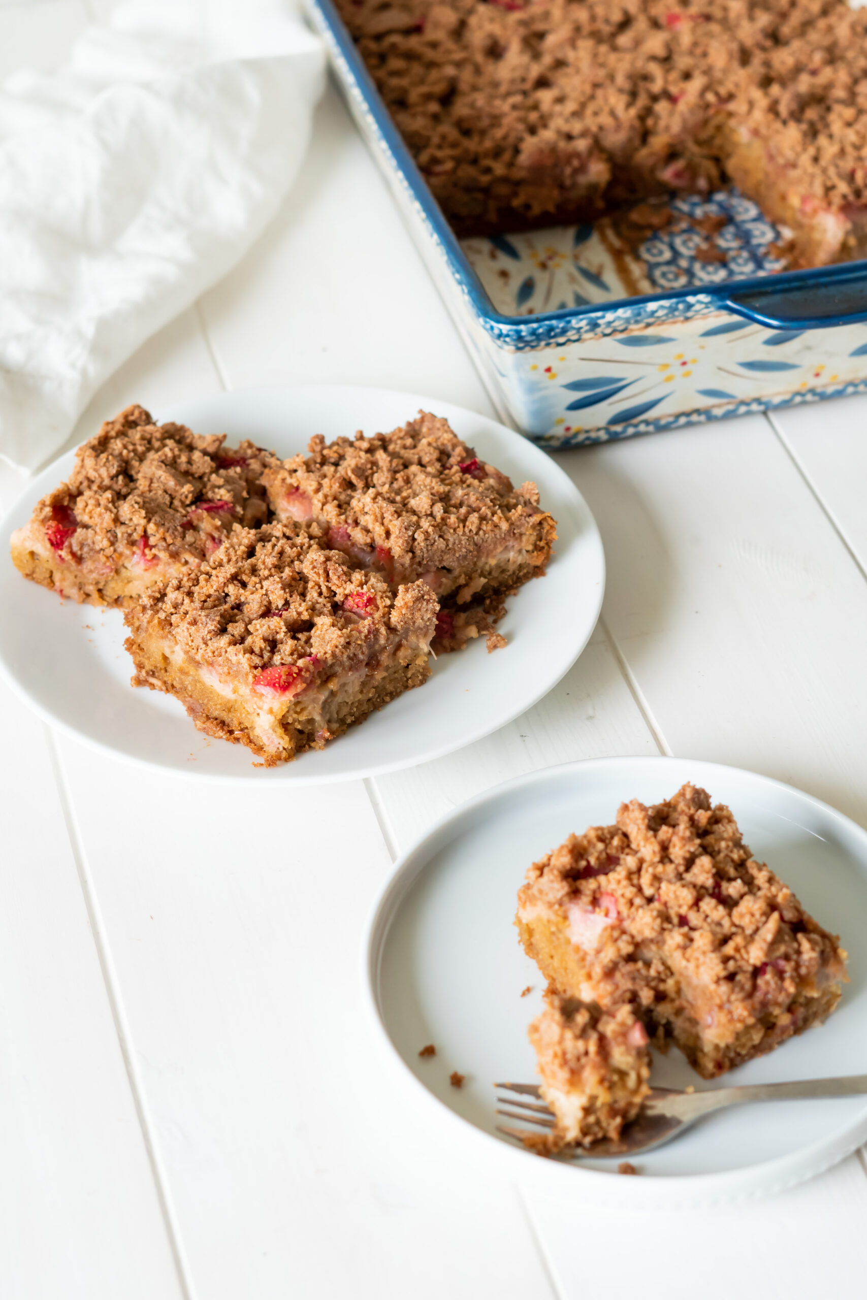 Three squares of rhubarb cake on a plate for serving.