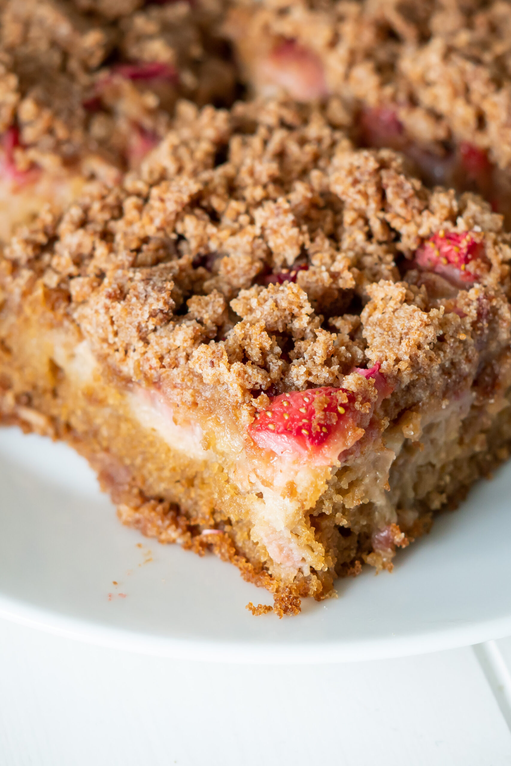 A zoomed in view of the corner of a piece of gluten free rhubarb cake to show the layers and crisp topping.