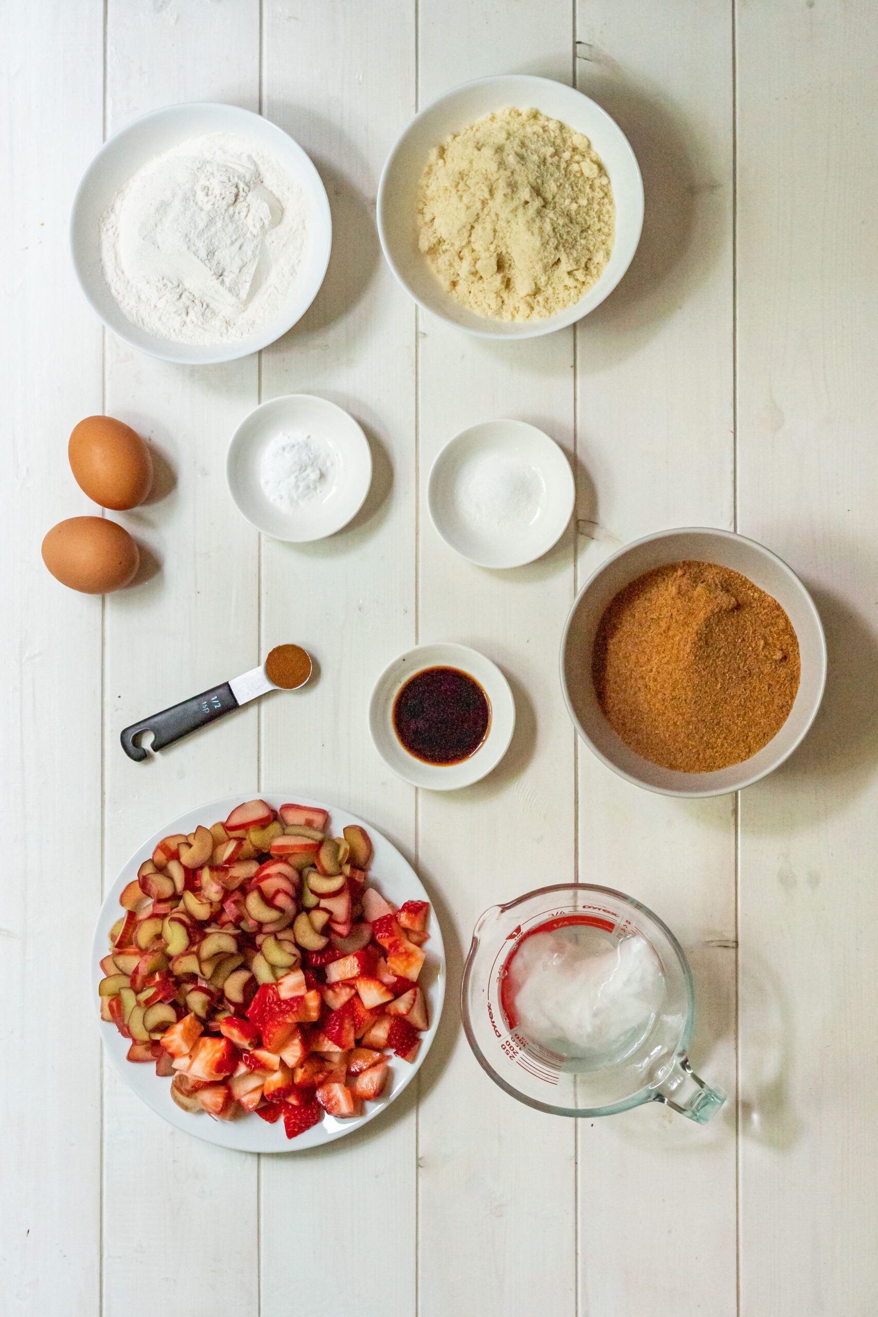 An overhead view of the 10 ingredients needed to make gluten free rhubarb cake.
