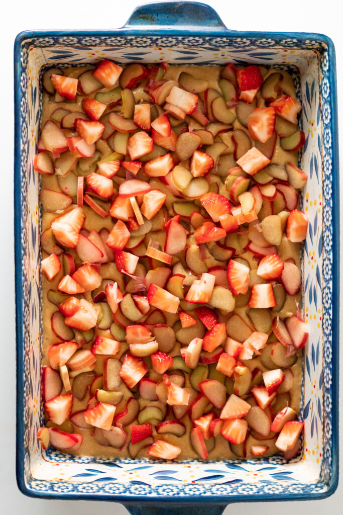 A 9 x 13 inch baking dish with batter and topped with fresh rhubarb and strawberries.