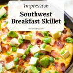 Side view of the Southwest Breakfast skillet in cast iron with bacon, avocado, and green onions on top!