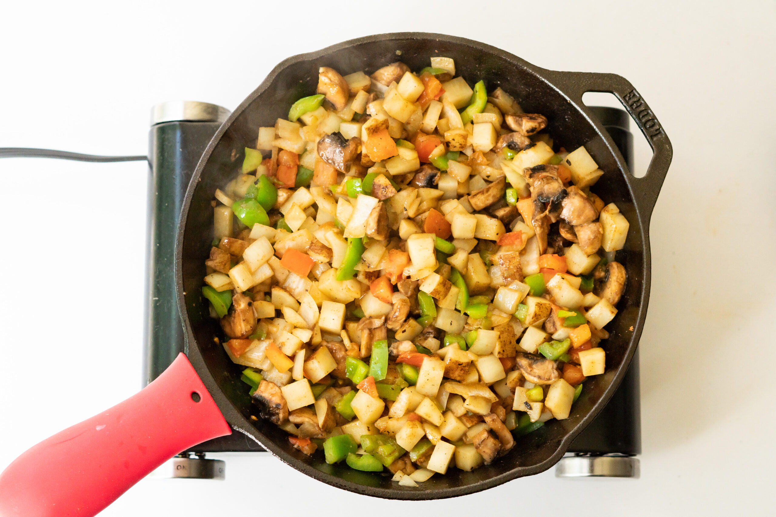 Overhead view of vegetables and potatoes fried with spices in a cast iron skillet.