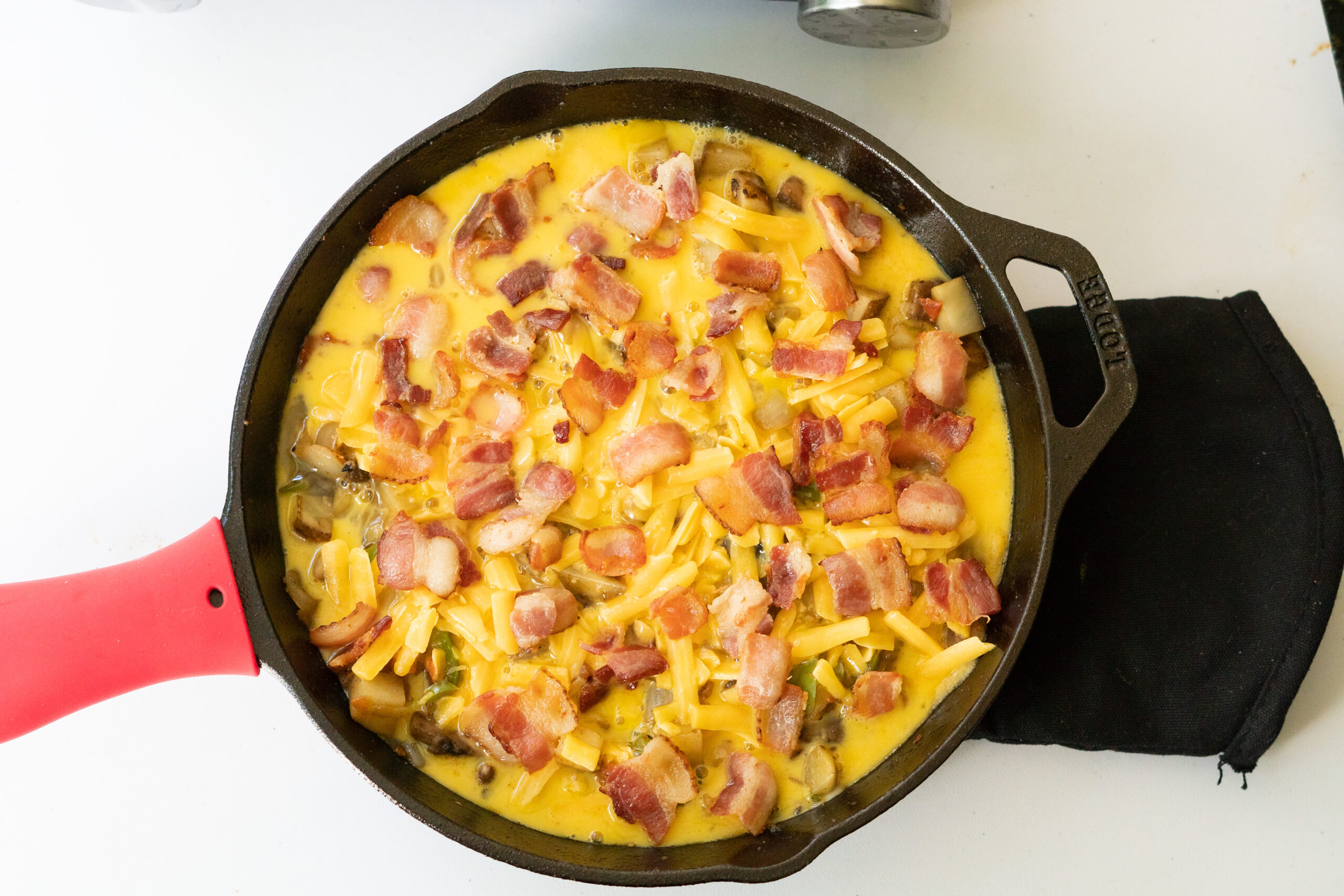 Southwest breakfast skillet ready for baking with vegetables, cheese, egg, and bacon layered in the skillet.