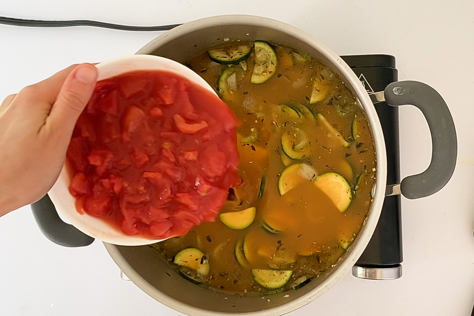 Overhead view of a hand adding canned diced tomatoes to the pot with veggies and broth.