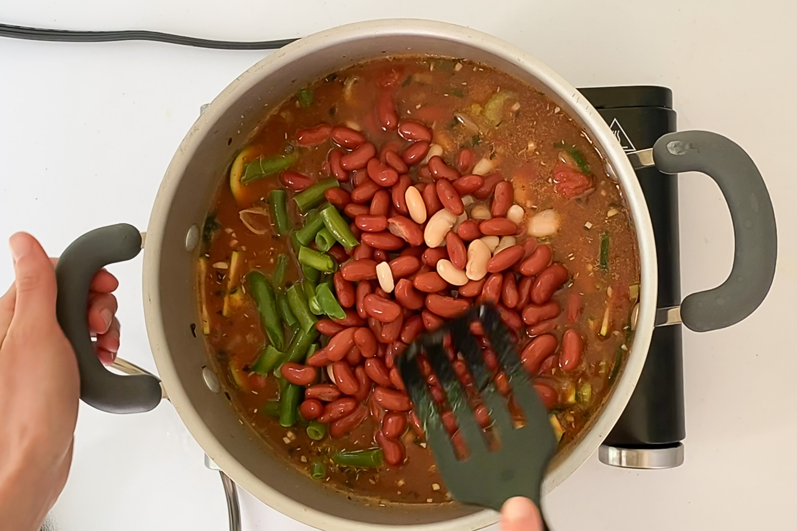 Overhead view of beans being added and stirred into the soup.