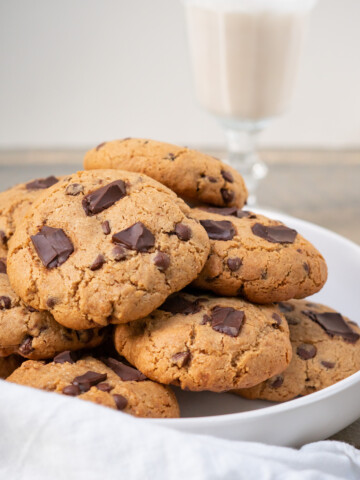 Side view of a plate of large soft almond flour chocolate chip cookies with a glass of dairy-free milk.