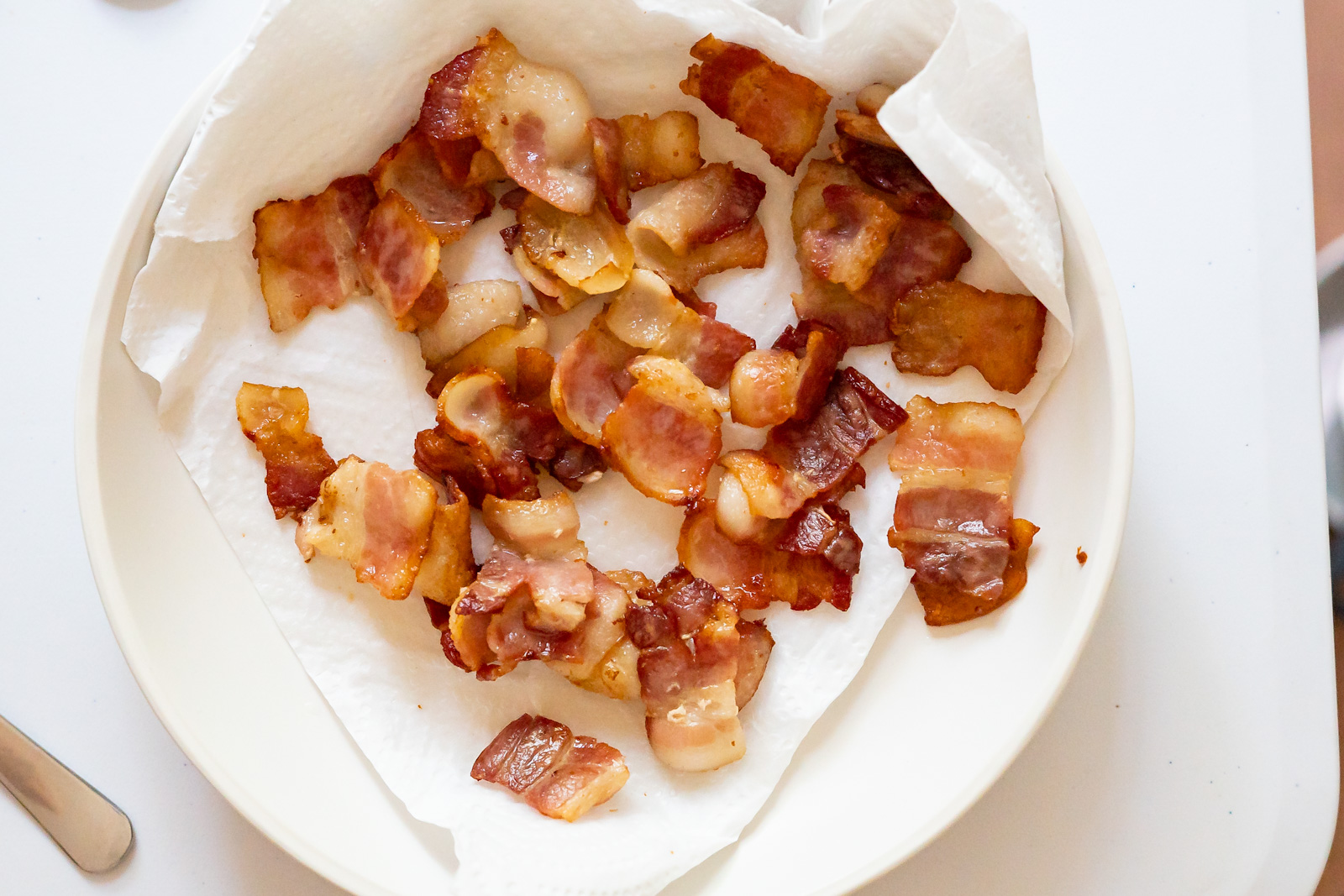 Overhead view of bacon pieces freshly crisped on a paper towel lined plate.
