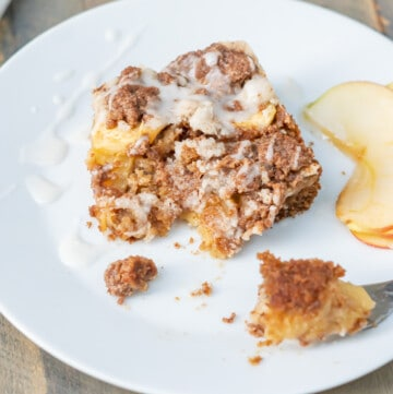 Side view of a slice of gluten-free apple coffee cake to show the three layers: cake, sliced apples, and crisp streusel.