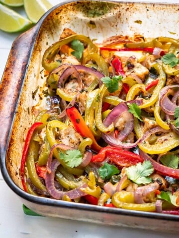 Side view of a glass dish of healthy baked chicken fajitas roasted to perfection and ready for serving with fresh cilantro and lime wedges on the side.